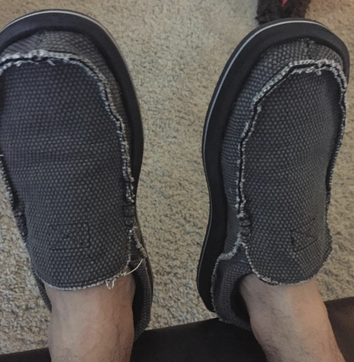 reviewer's feet wearing the shoes in gray. they have a loafer style so they are flat and low-top but cover the foot entirely.