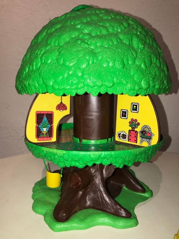 A tree house play set were top of the tree lifts to reveal a house inside.