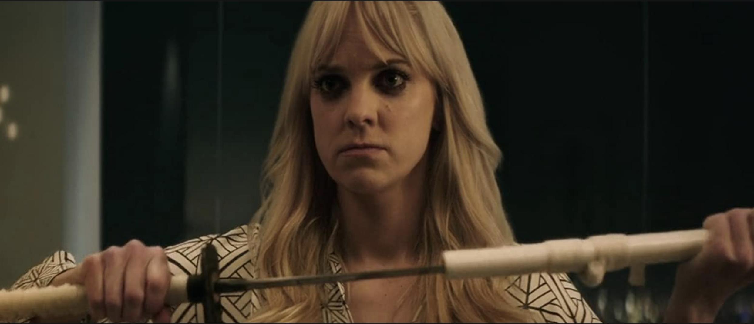 A wild-eyed Anna Farris unsheathing a Japanese sword