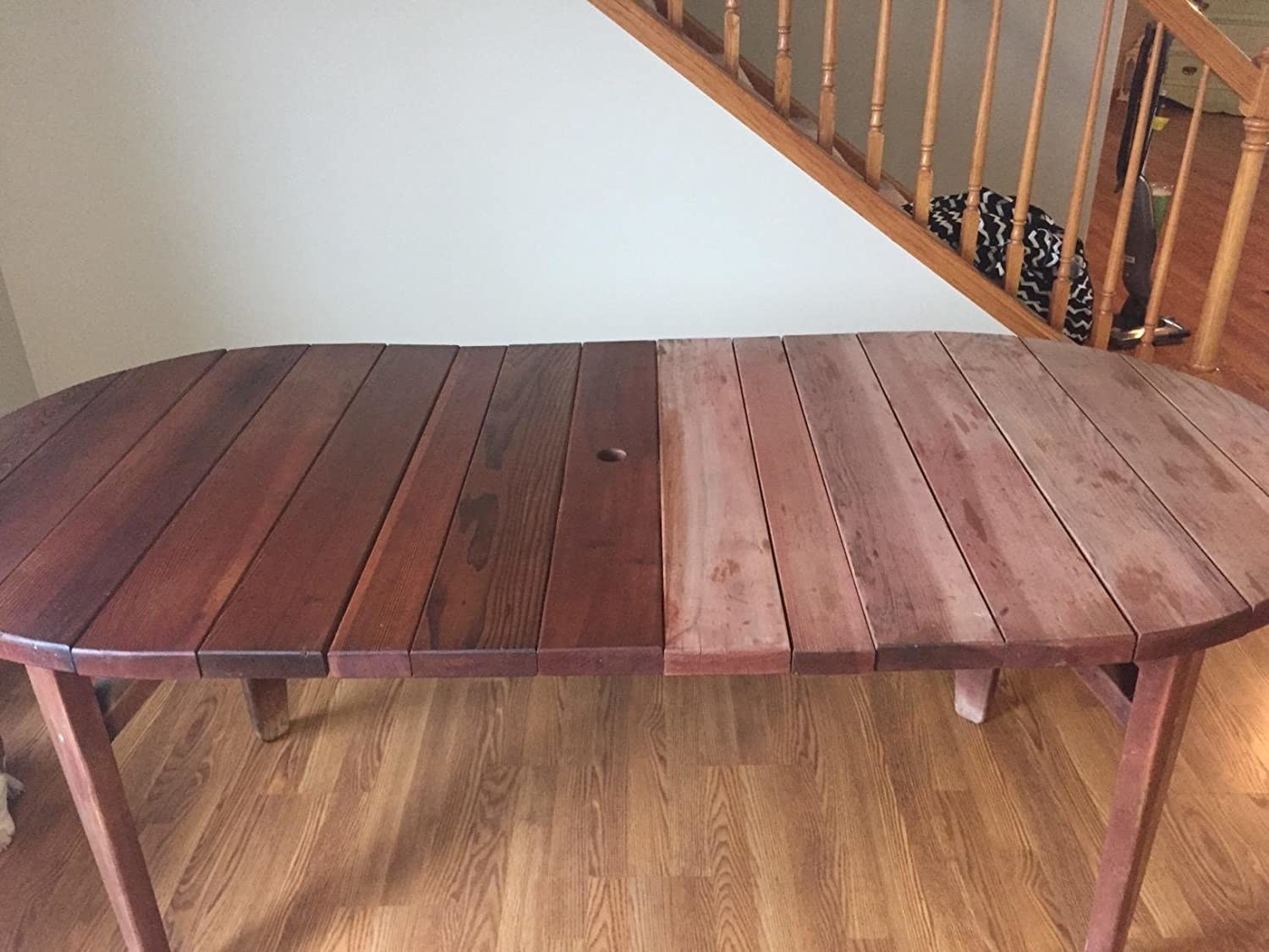 An outdoor teakwood table, half looking dried out and worn, the other half treated with the product and looking rich, hydrated, and dark