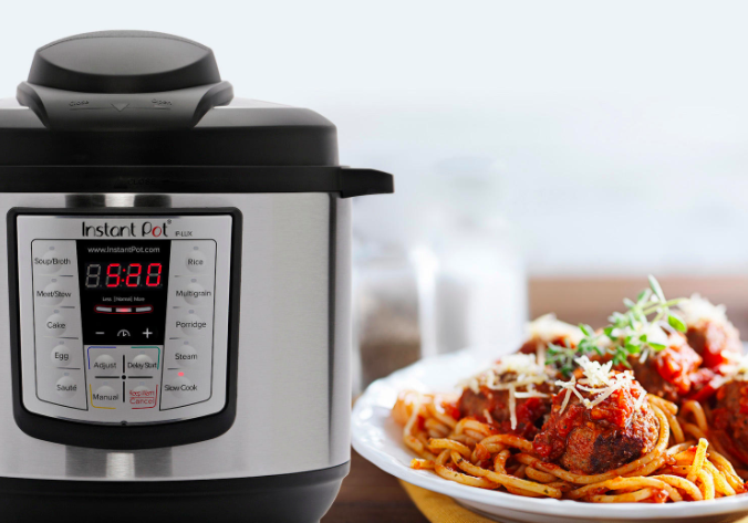 An Instant Pot pressure cooker next to a plate filled with spaghetti and meatballs