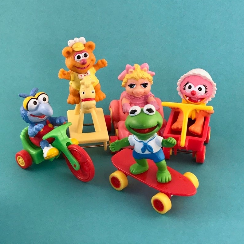 Five Muppet Babies (Gonzo, Fozzie, Piggy, Animal, and Kermit) Happy Meal toys displayed against a teal back drop.