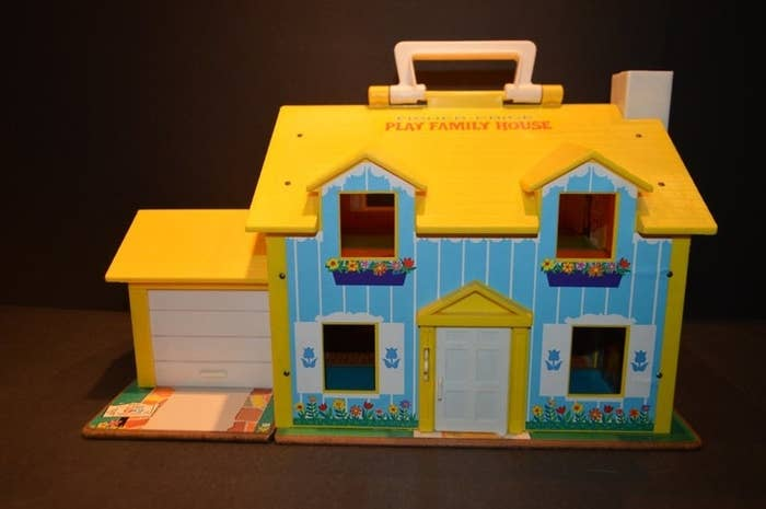 A Fisher-Price Little People play house with a yellow roof and blue walls.