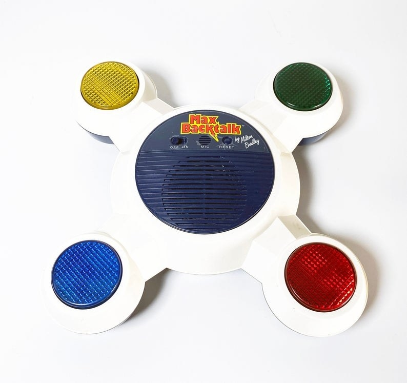 A Max Backtalk game which is white and features four different colored lights (yellow, green, red, and blue) on extended arms.