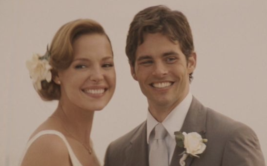 Jane and Kevin smiling in their wedding outfits with flowers adorning them