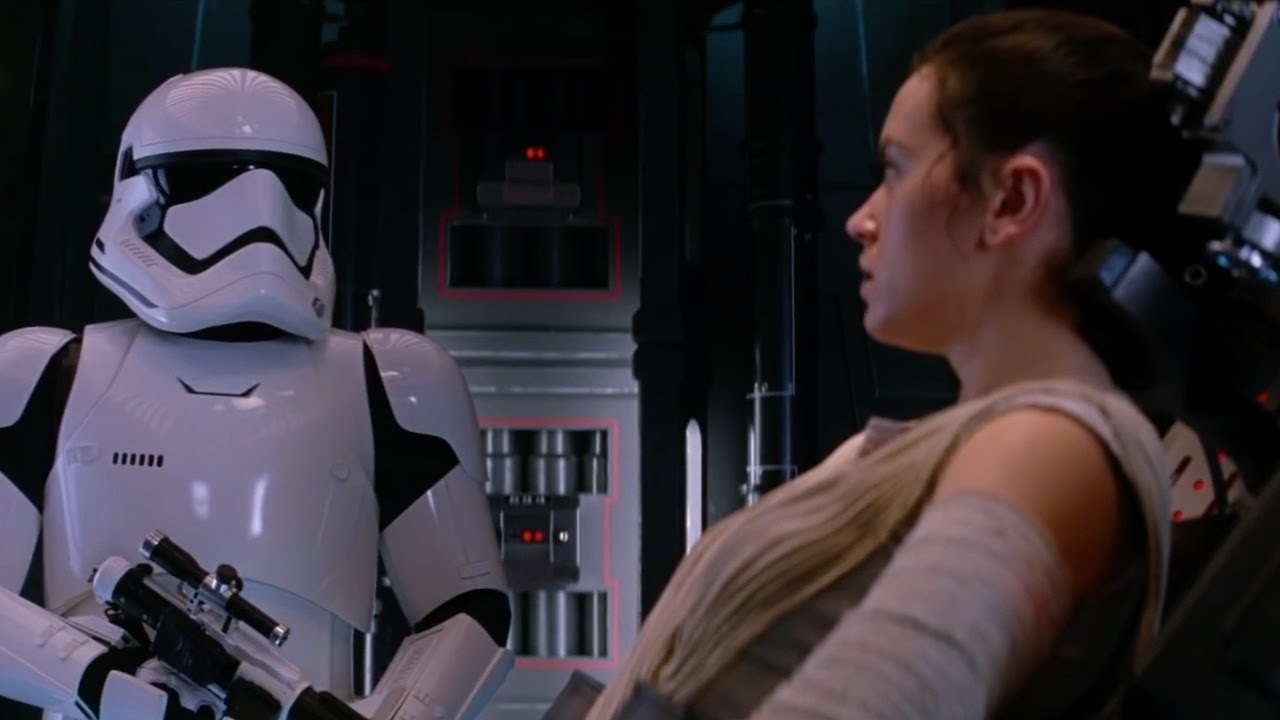 A stormtrooper stands over a captive Rey