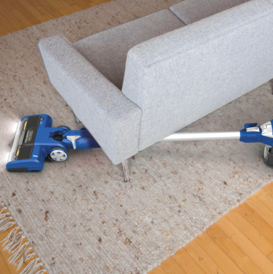 Blue vacuum lifts up dust from a carpet under a couch