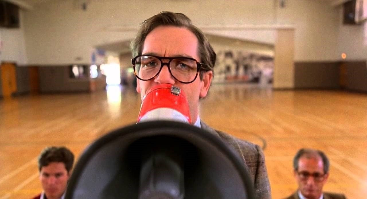 A straight-laced looking Huey Lewis holds up a bullhorn in a gymnasiun