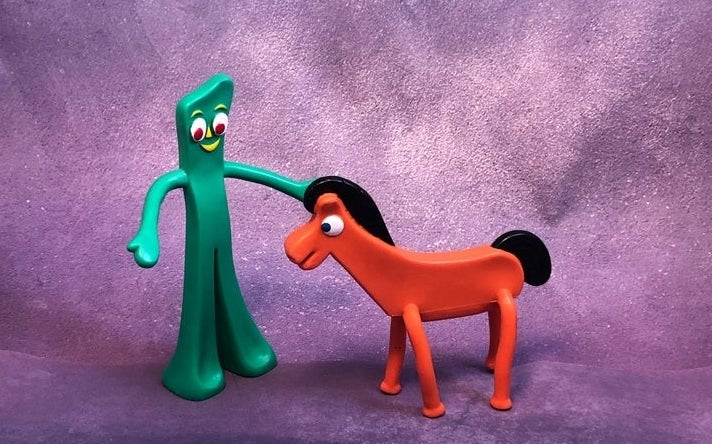 Gumby and Pokey figures standing against a purple backdrop.