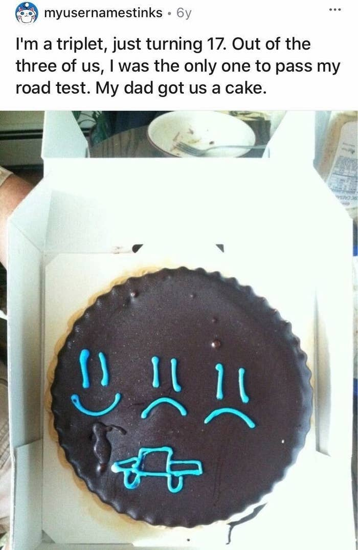 A cake decorated with two sad faces and one happy face gifted by a dad to his triplets for taking their driving test