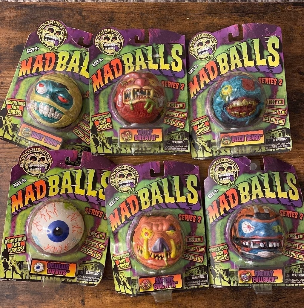 Six different Madballs in its original packaging on a wooden table.