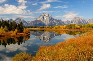 beautiful mountain range with fall foliage reflected in a lake