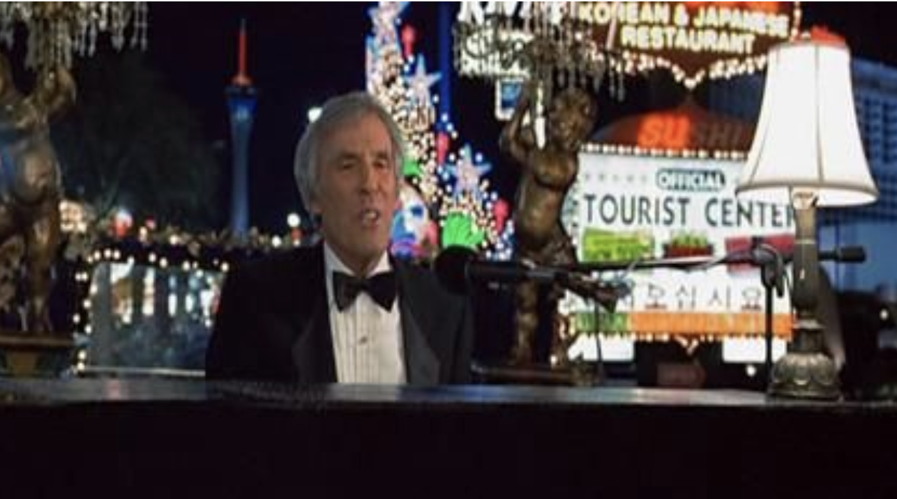 A tuxedoed Burt Bacharach playing a piano in Las Vegas