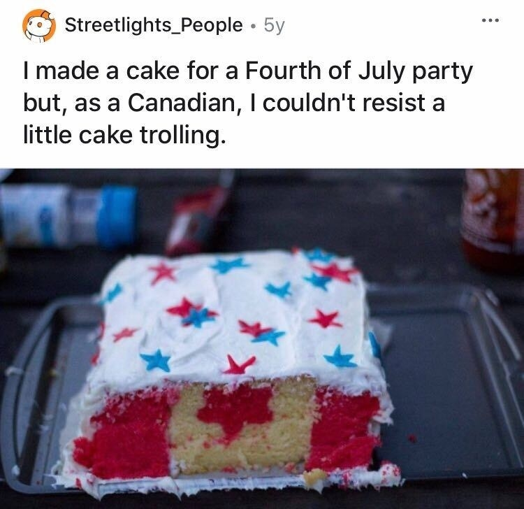 A cake decorated in blue frosting and red and blue stars, but looks like the Canadian flag from the inside