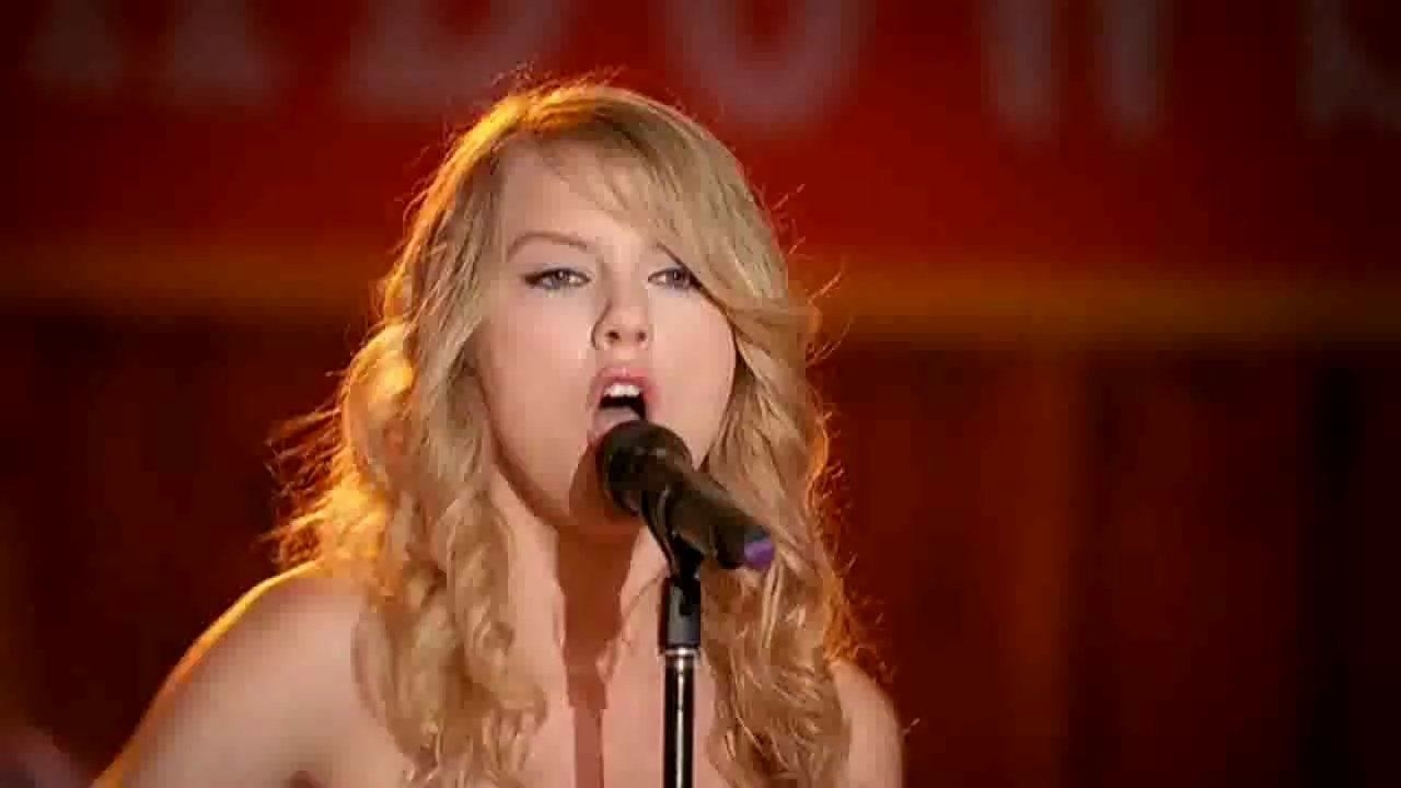 Taylor Swift sings at a microphone