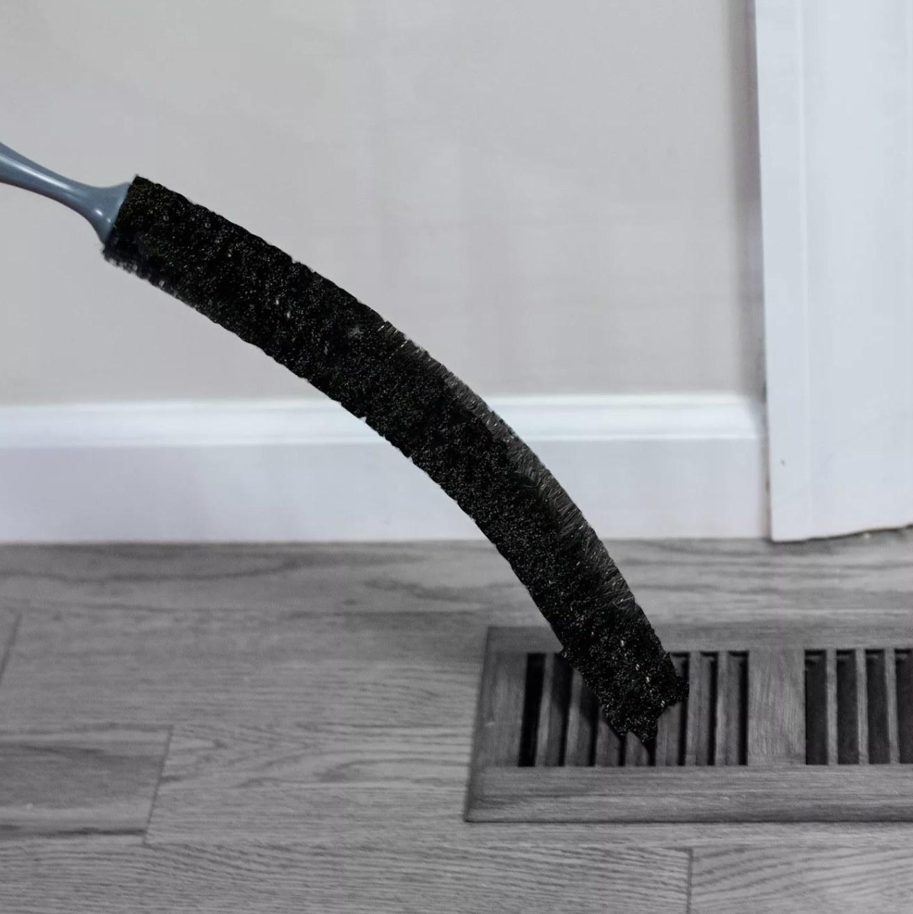 Black bristled brush sweeps dust out of a hardwood floor radiator