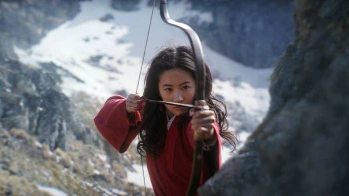 Mulan aiming to shoot someone with a bow and arrow