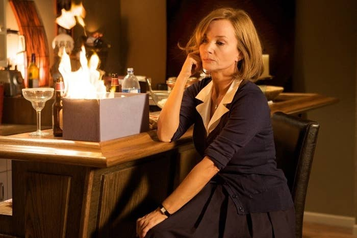 A woman sitting nonchalantly at a bar as a box in front of her is set on fire