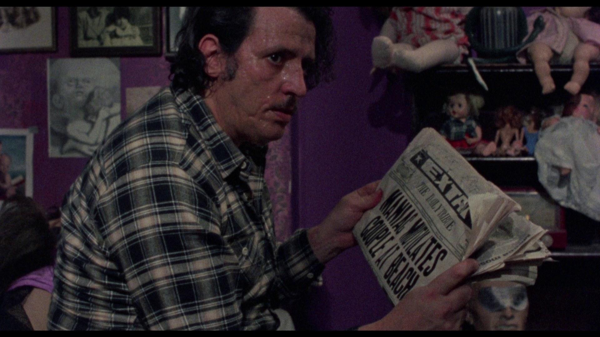 A creepy man reading a newspaper about horrific, murderous events