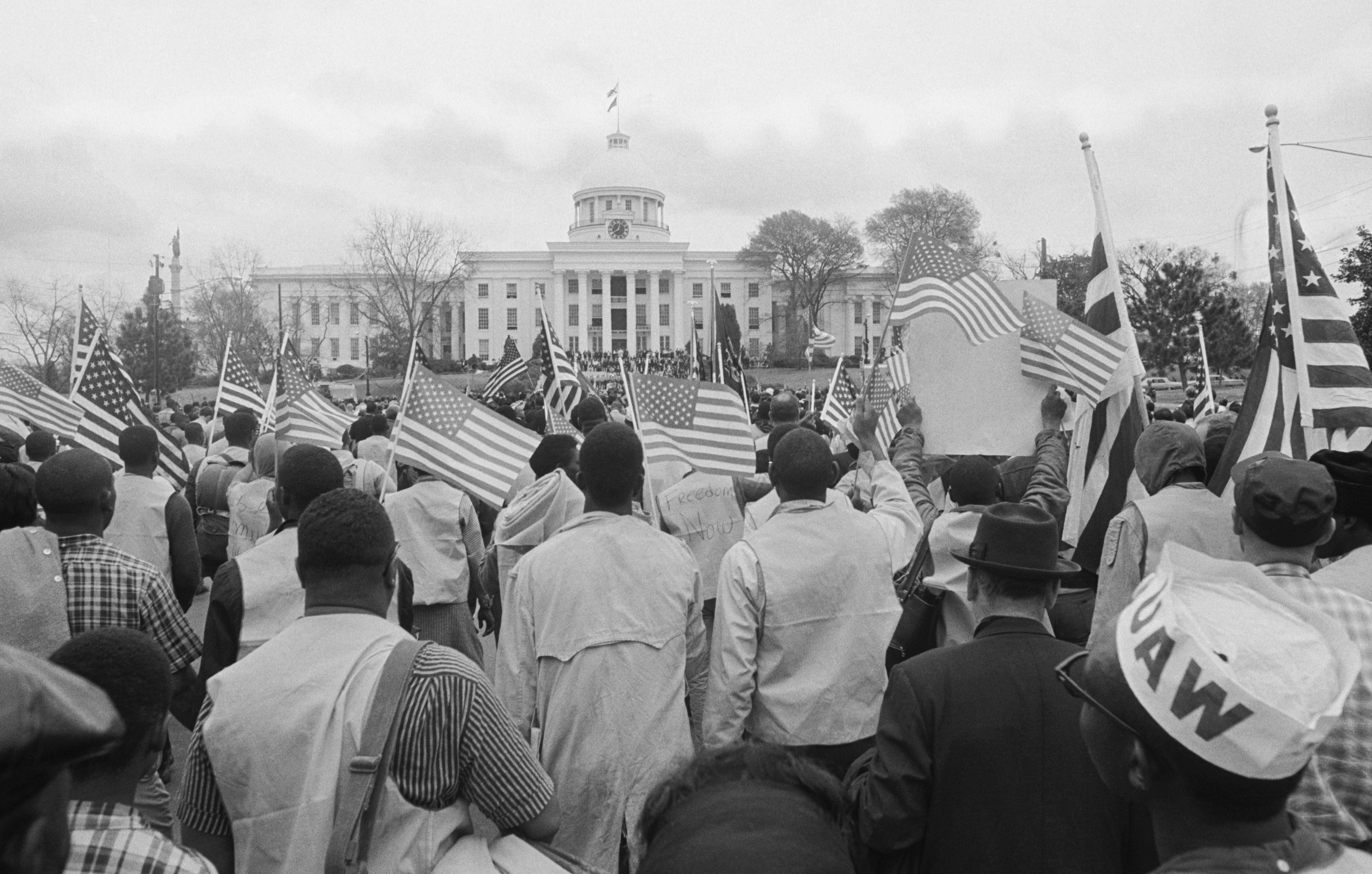 A crowd of black men and women carrying American flags are seen from behind as they stand in front of the capitol building in Alabama