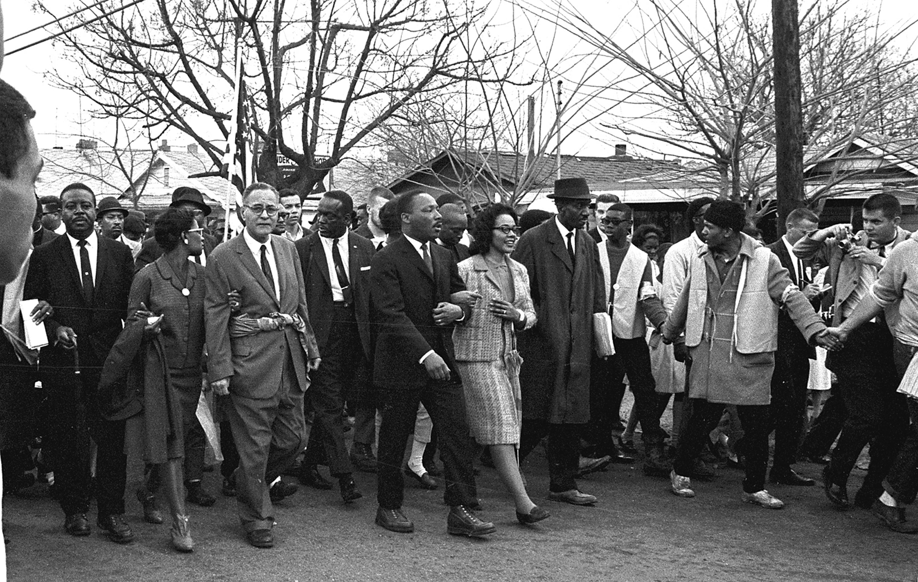 Martin Luther King Jr. and his wife lead a march of black and white people dressed nicely down the street