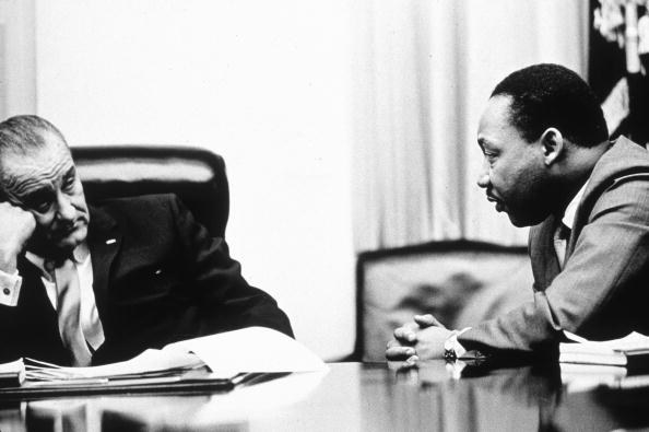 Lyndon Johnson leans on his hand in front of a pile of papers on the table in front of him while Martin Luther King Jr. leans in to talk to him