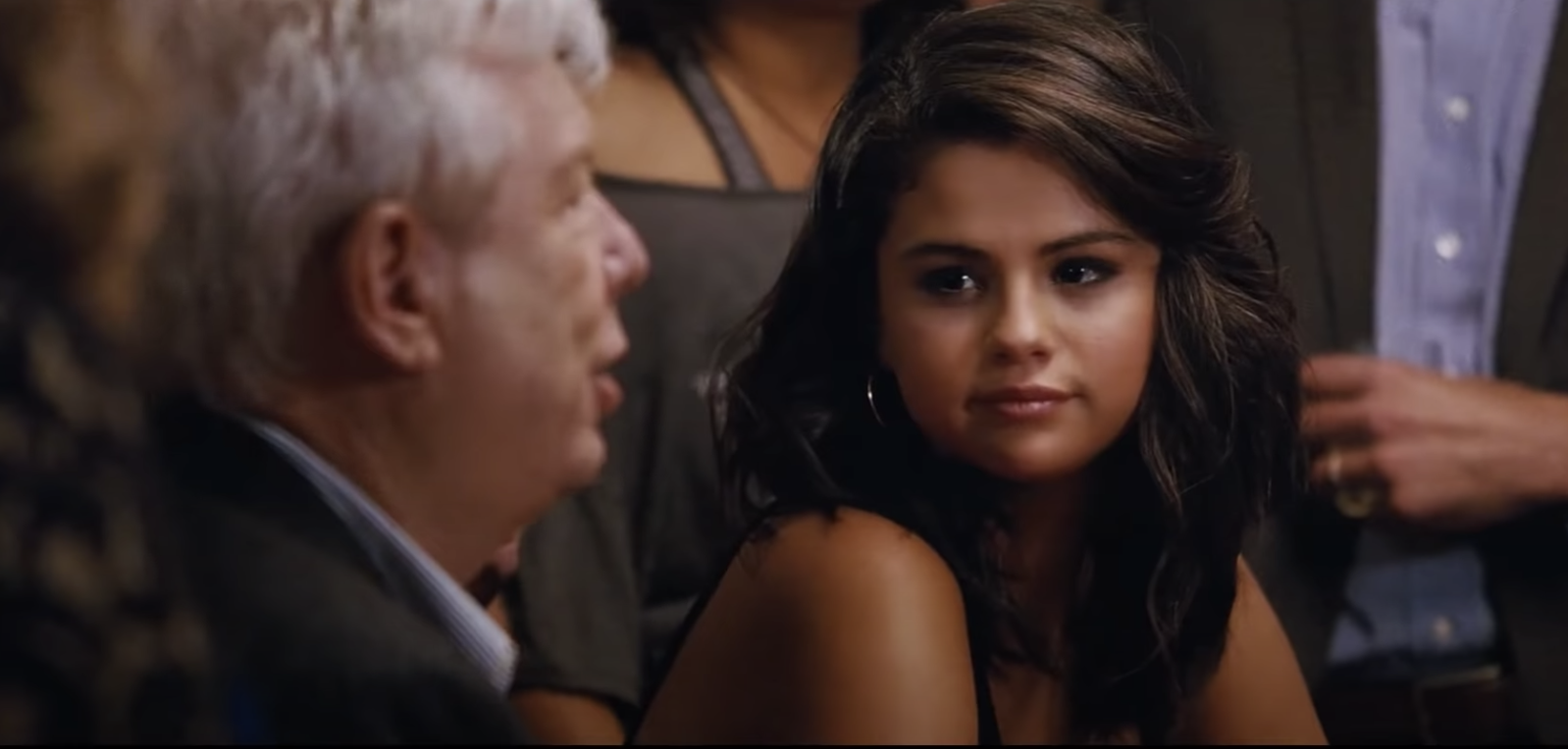Selena Gomez sitting at a card table