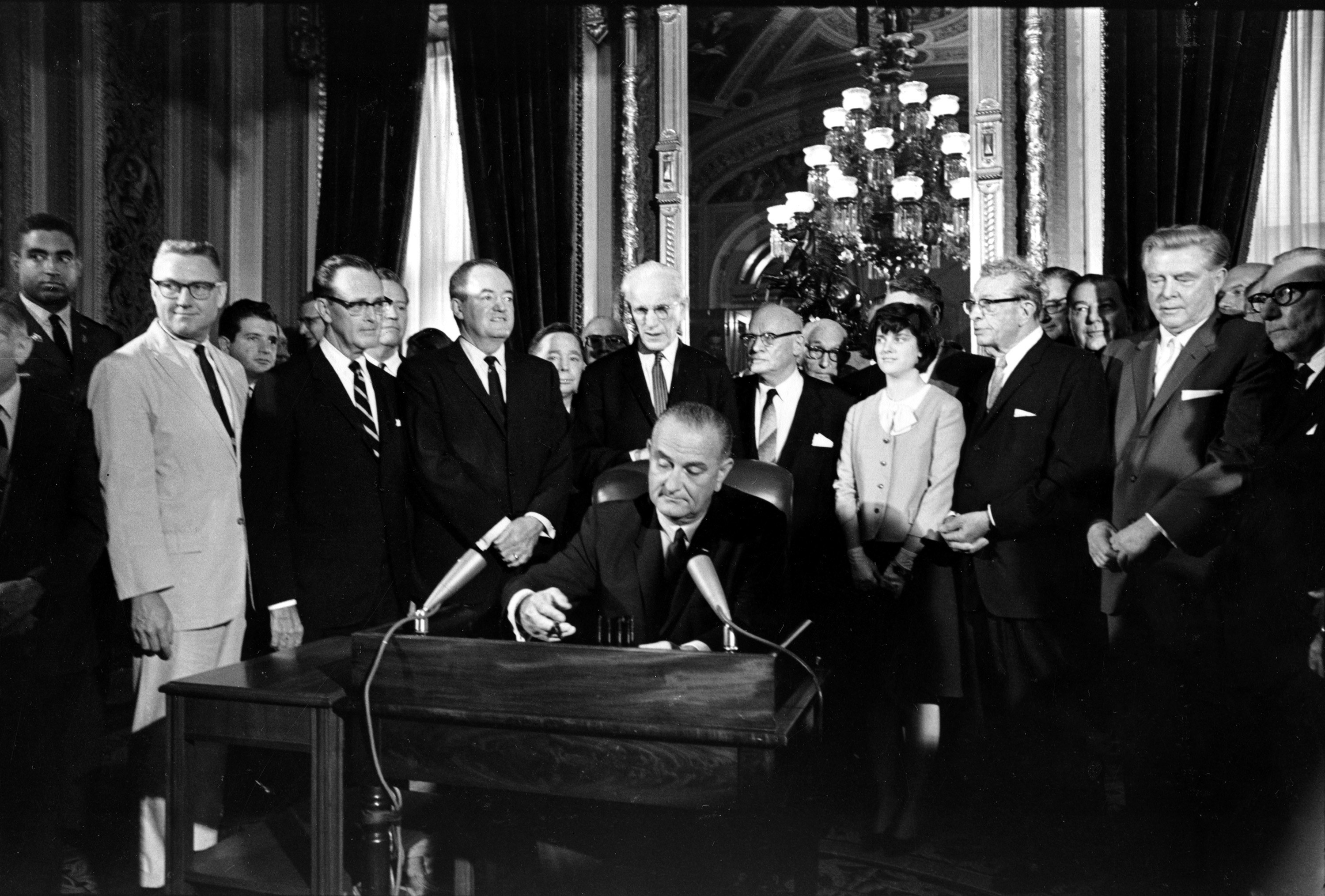 President Lyndon B. Johnson sits at a desk surrounded by white men in suits