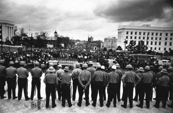 A line of police officers is seen from behind as they face a crowd in front of the capitol building in Alabama