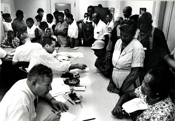 Black men and women stand at a table while white men sit behind it with registration papers.