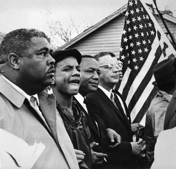 A group of five men, four black and one white, walk arm in arm down the street with an American flag