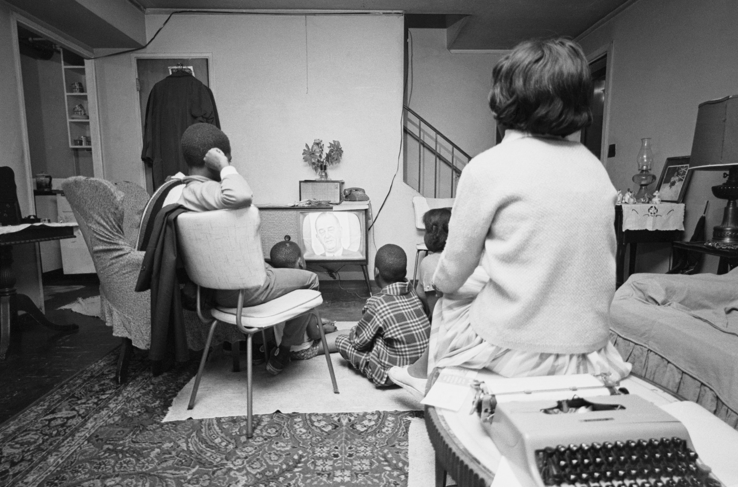A Black family is seen in a living room watching television