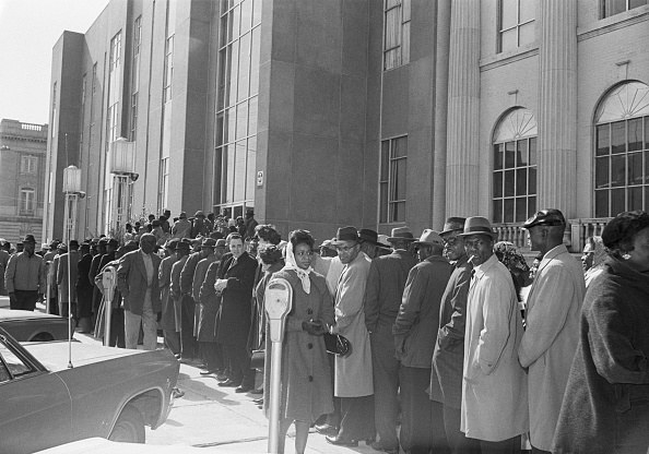 A long line of people in coats stand in front of the courthouse