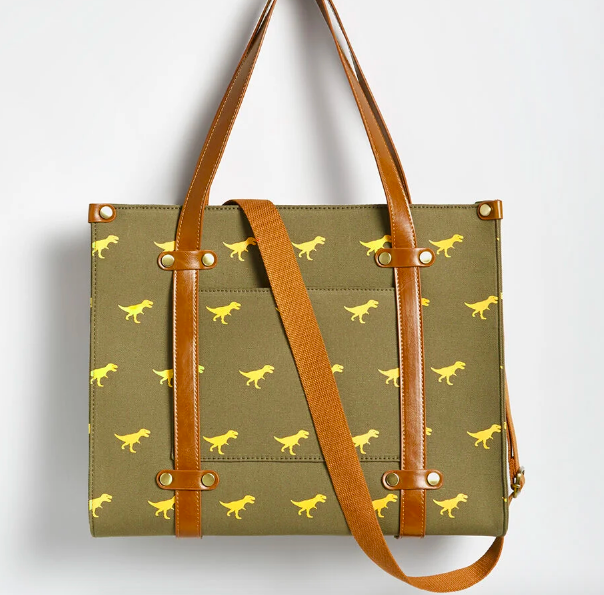 An olive green tote with warm faux-leather straps and gold button hardware. It has a pocket on the outside, a zipper at the top, and a tiny golden T-Rex pattern throughout the fabric.
