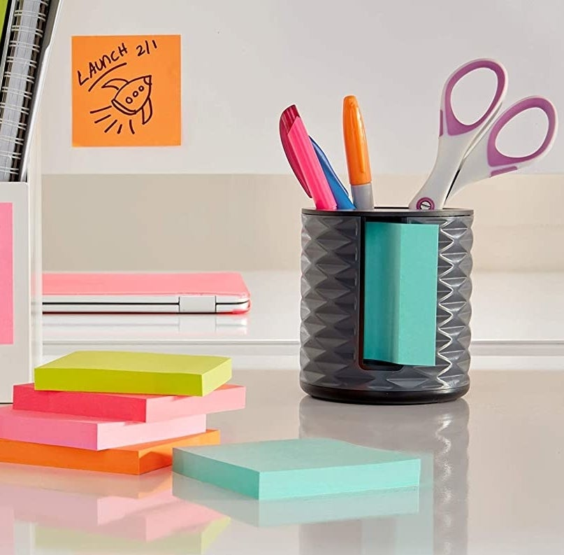 The sticky note dispenser holding markers and stickers next to a stack of sticky notes