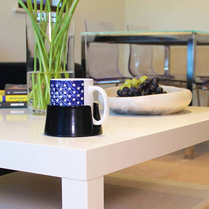 The anti-spill drink holder on a coffee table with a mug inside of it