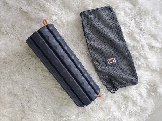 Reviewer's picture of the black foam roller with its slipcover