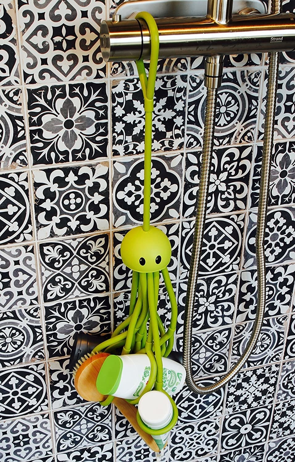 A hanging rubber octopus with several tentacles with round grippy ends. It is holding a brush, conditioner, shampoo, cleanser, and has room for more products.
