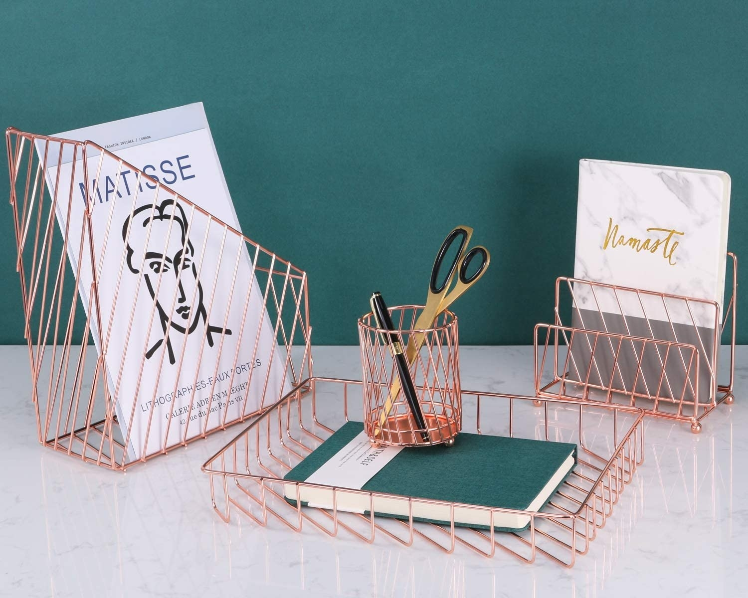 A wiry rectangular magazine holder with a single magazine in it, a rectangular document tray with a book in it, a cylinder pencil holder with a pen and pair of scissors in it, and a letter tray with a notebook in the second slot
