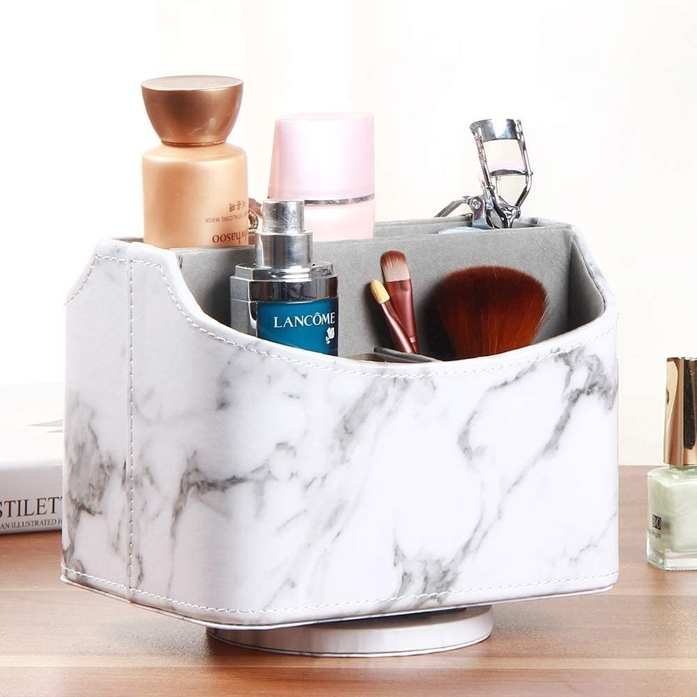 A spinning caddy on a desktop filled with makeup brushes skincare and an eyelash curler