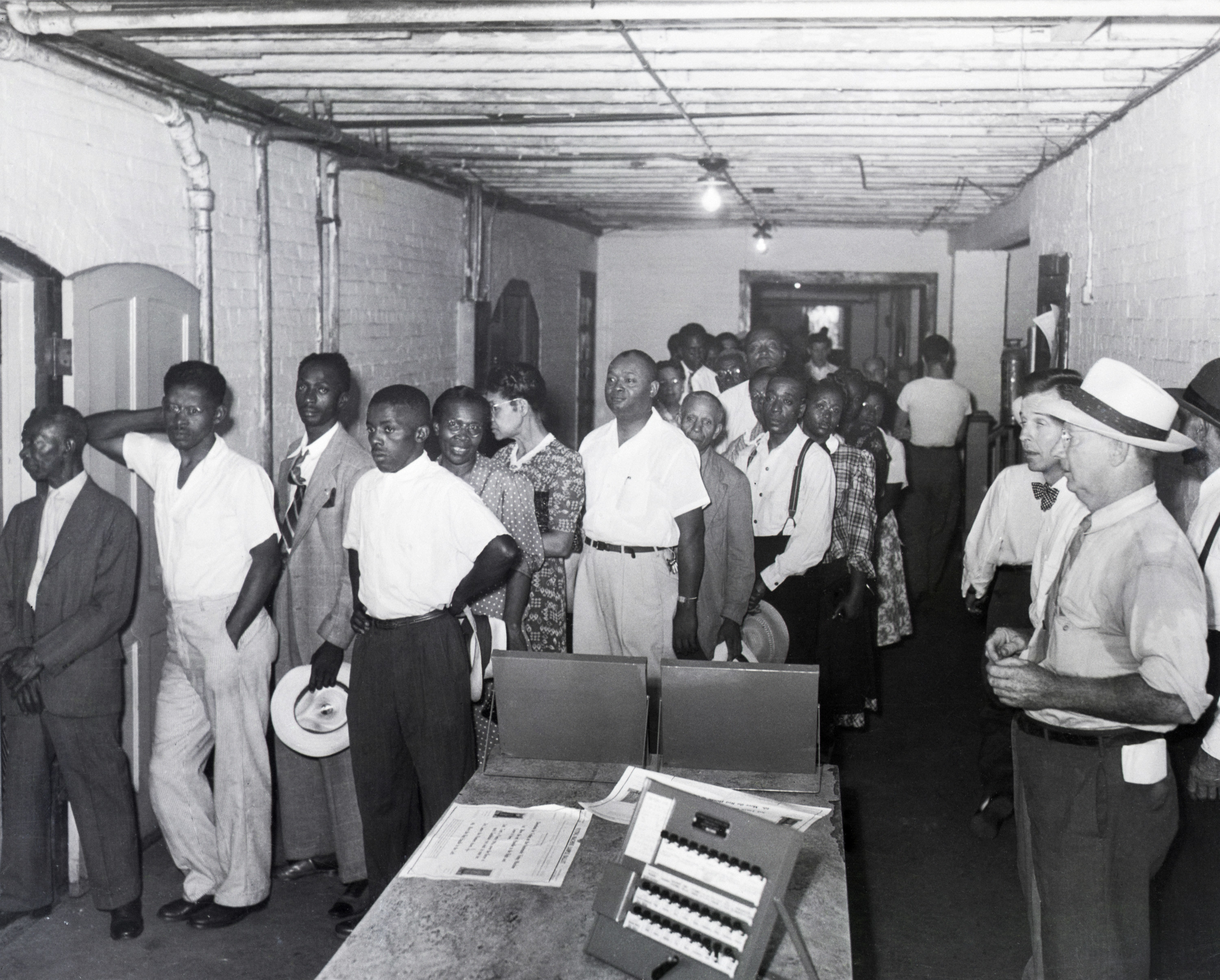 Black men line up, holding hats and dressed nicely, in a room where they are watched by white people