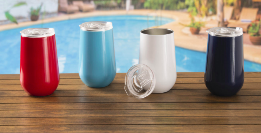 Red, blue, white, and black drink tumblers on a pool deck