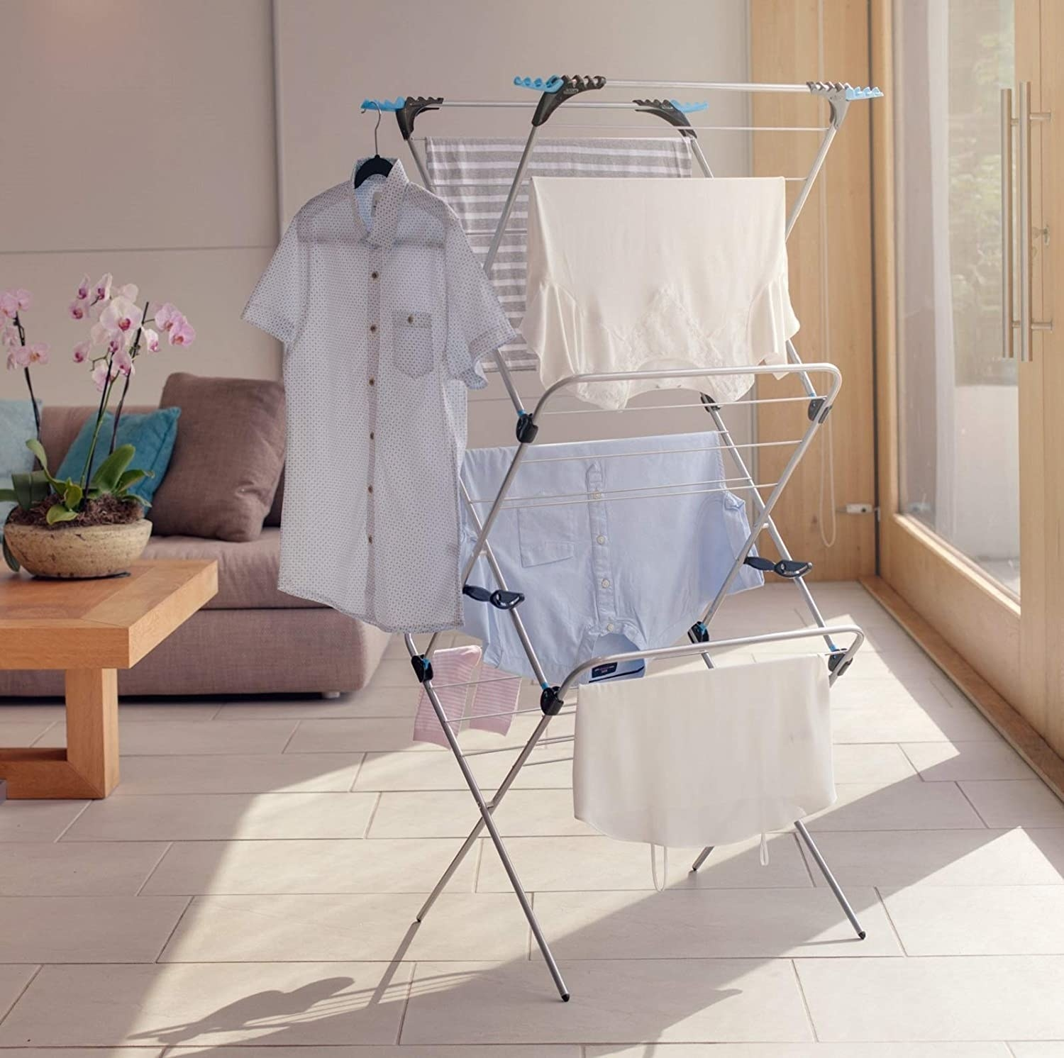 Three-tiered drying rack with clothes hanging on it in living room