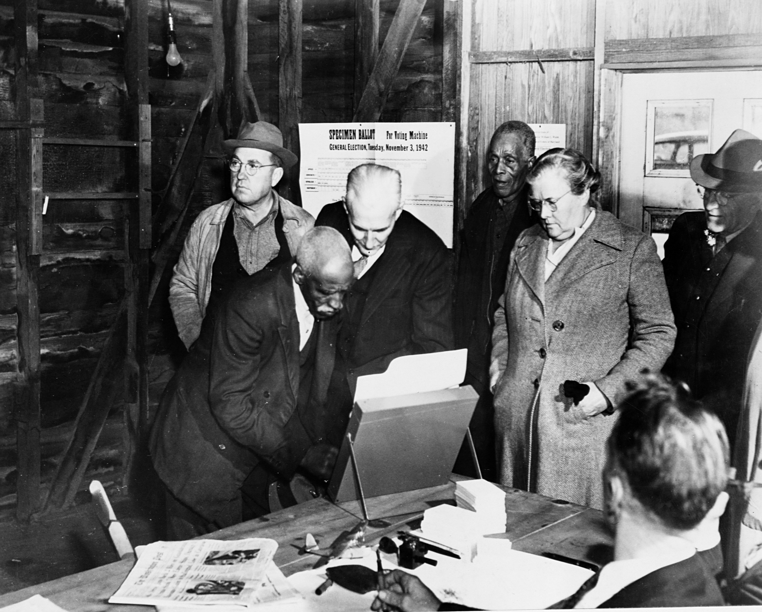 An elderly black man at the ballot box while a line of white and black people in overcoats wait behind him
