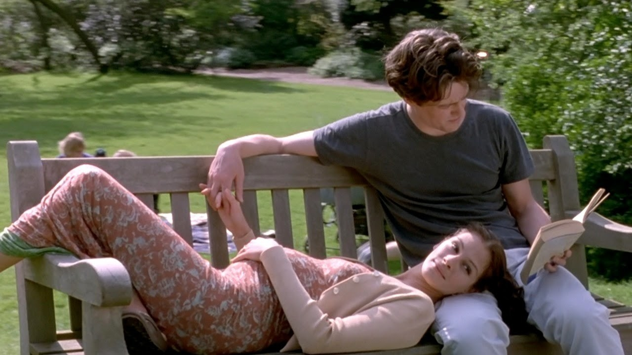 A pregnant Anna and Will sitting outside on a park bench