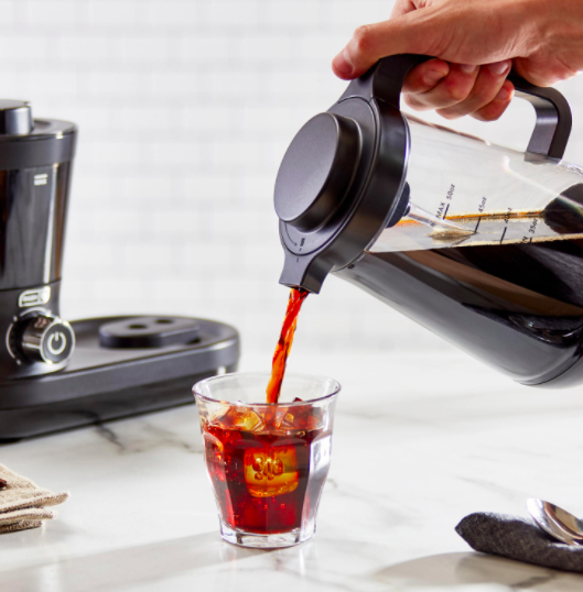 Hand pours cold brew into cup from black rapid cold brew system on a countertop