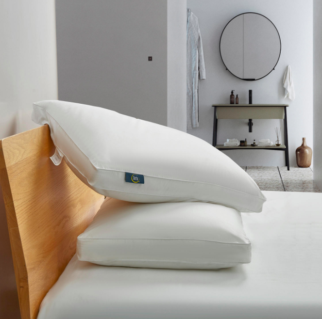 Two white side sleeper pillows propped against a wood headboard and white mattress in a bedroom