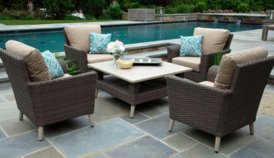 Wicker patio furniture set with four chairs and a nude-colored table near a pool