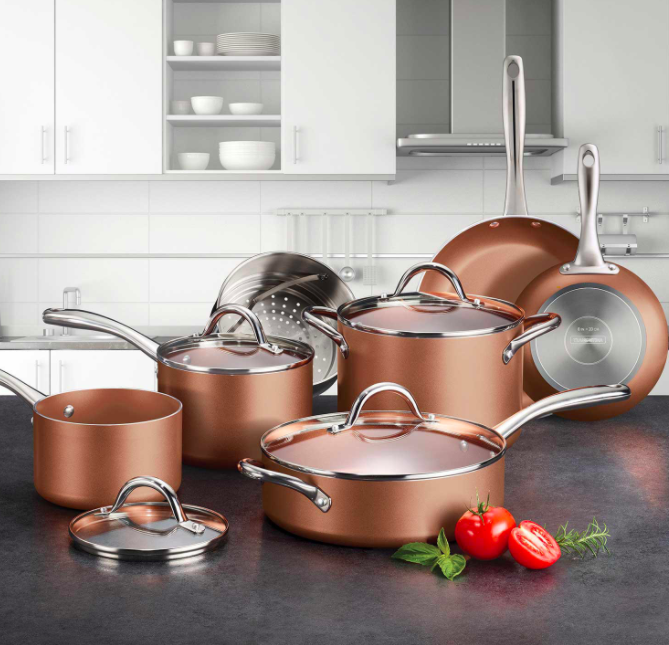 Copper cookware set that includes skillets, pans, and pots on a kitchen counter