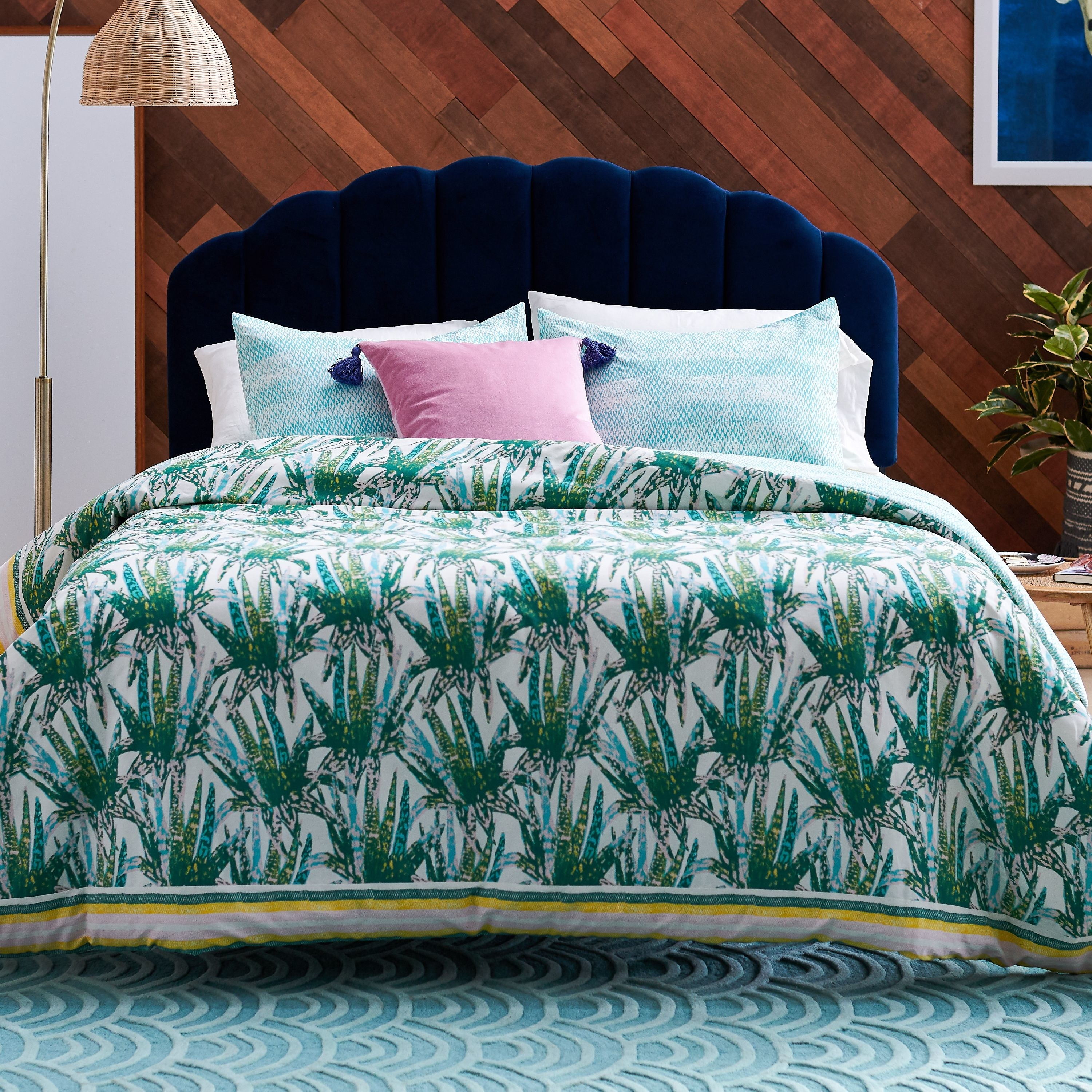 The comforter with a green and blue succulent illustration all over it on a bed with assorted pillows